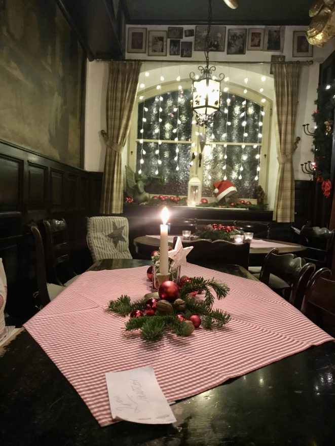A cosy wine tavern scene: Christmas lights on the window and a red and white checked table cloth with a candle on a wooden table