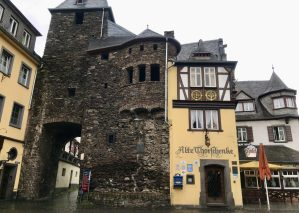 Part of Cochem's old stone fortifications and a yellow timber-framed house on a grey day