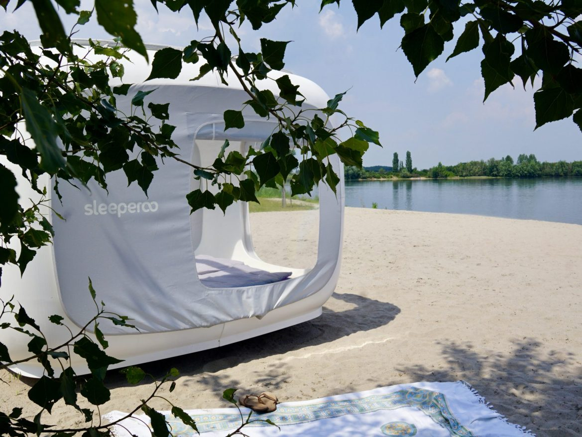 A Sleeperoo sleeping cube from the side/behind looking onto a beach at a lake