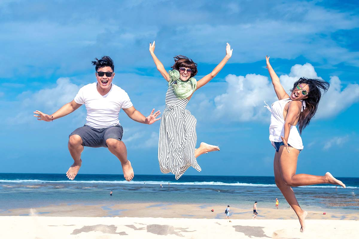 people, freedom, happiness and teenage concept - drug addiction recovery a group of happy friends in sunglasses jumping high over blue sky and beach background