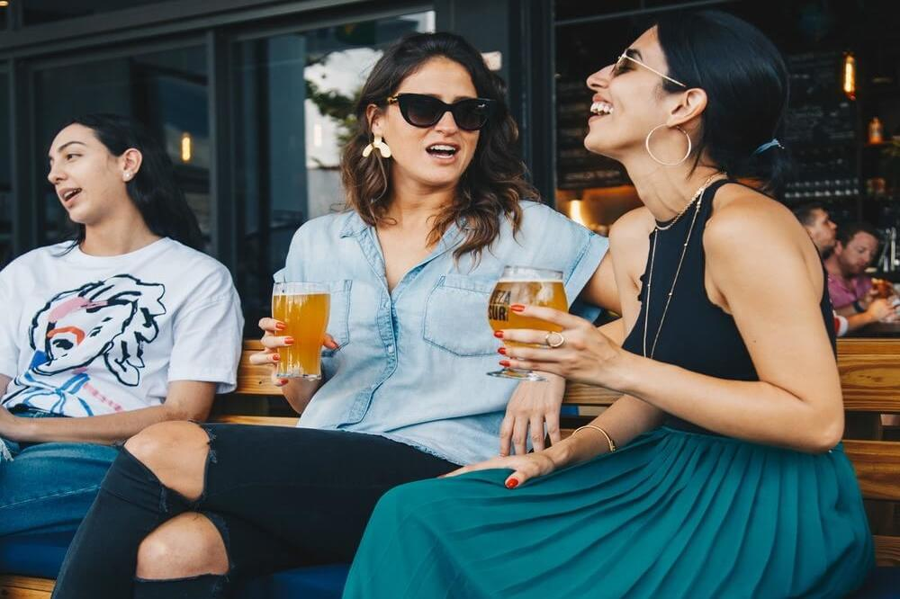Female friends cheering with beer at music festival, alcohol and drug recovery center