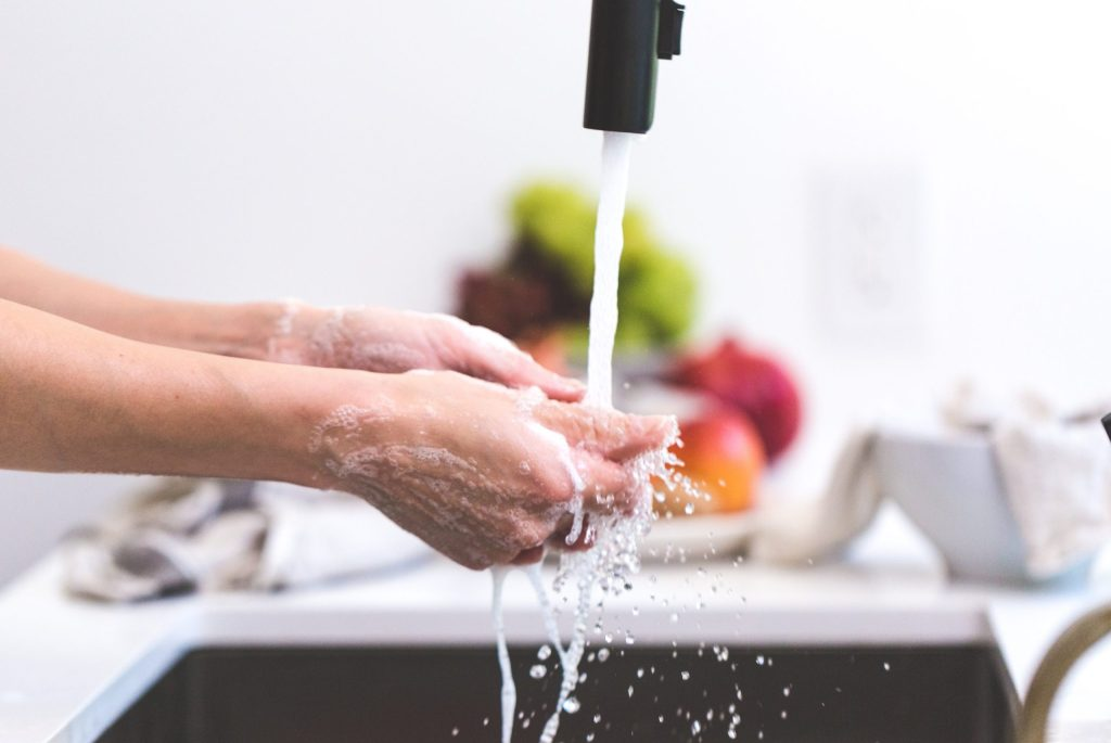 washing hands under a faucet