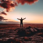 man with arm's outstretched with sunset in background
