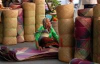 A woman selling Tikar Lampit, an Indonesian handicraft from South Kalimantan