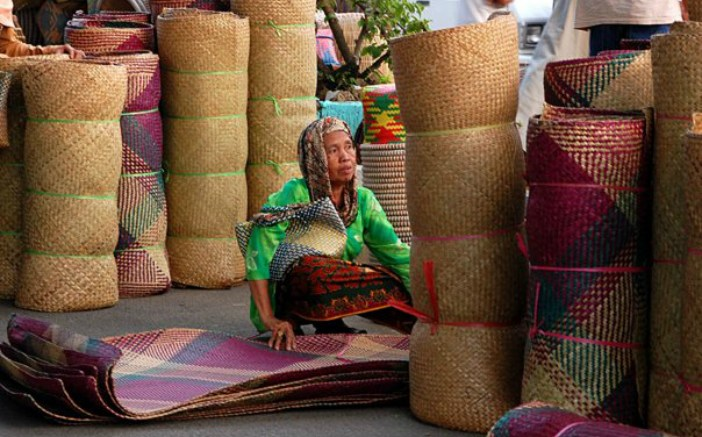 A woman selling Tikar Lampit, an Indonesian handicraft from South Kalimantan