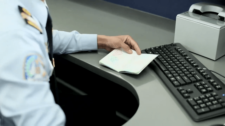 Indonesia Immigration Officer stamps a passport at an airport