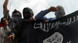 Islamic state fighters hold up the ISIS flag