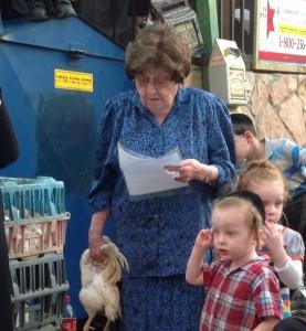 Sa poule à la main, ses petits enfants à ses côtés, les kapparot de la dame en bleu
