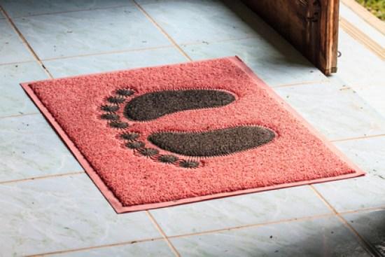 foot on doormat with open door close up