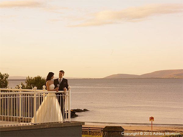 Bride and Groom standing on the balcony looking out over Galway Bay at the Galway Bay Hotel on the promenade at Salthill.