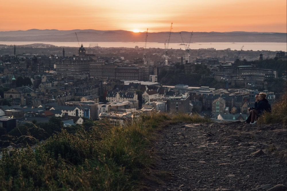 Two people sitting at the top of Calton Hill watching the sunset