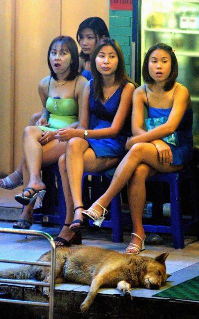 Ragazze thailandesi aspettano i clienti fuori da un go-go bar in un quartiere a luci rosse di Bangkok - Getty Images
