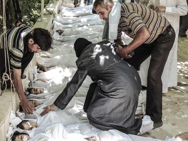 Una madre e un padre piangono sul corpo del del figlio ucciso in un attacco con armi chimiche a Ghuta, un sobborgo di Damasco. Foto AP