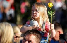 Three-year-old Ruby Tindall holds a rose as she takes part in a vigil for the victims of an attack on concert goers at Manchester Arena, in Royton, near Manchester, Britain May 26, 2017. REUTERS/Phil Noble