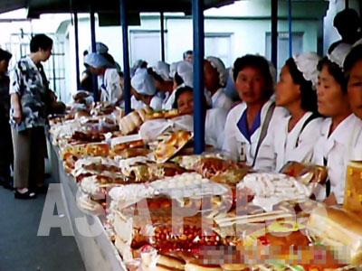 市場でパンや菓子を売る女性たちは雇われではなく幅80センチの売場の主。とても商売熱心な上愛想も良い。(2011年6月平壌市の牡丹(モラン)市場 ク・グァンホ撮影)