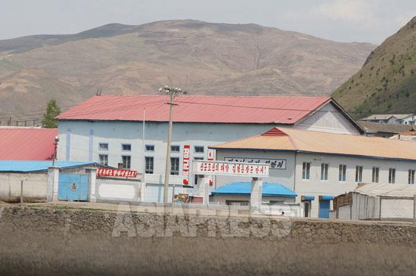 荒廃した北朝鮮の山1 偶像化のためのスローガンが立ち並ぶ建物の後ろに、山頂まで耕されたはげ山が見える。両江道恵山(ヘサン)市。2014年5月中旬、朝中国境地域の中国側から撮影。