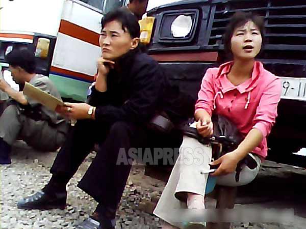 客を待つバスの車掌の女性。時刻表はなく座席が埋まると出発する。(2013年9月沙里院市 リ・フン撮影)】