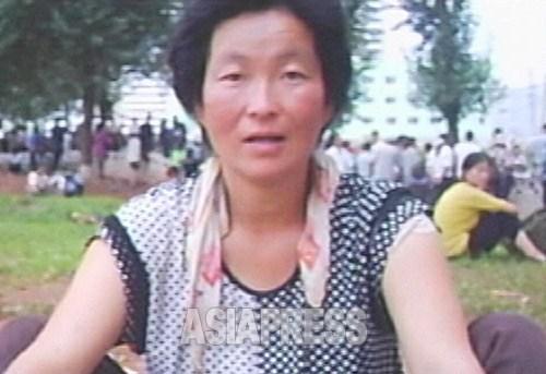 아파트 가의 광장은 장사 때문에 모인 인파로 북적였다. '사세요'라고 촬영자에게 말을 거는 음식 장사꾼 여성. 2007년 8월 하순 평양시 낙랑구역에서 촬영 리 준(아시아프레스)