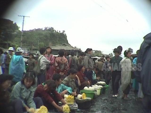 배급제의 파탄으로 유일한 물류거점이 된 암시장에 인파가 몰렸다. 상행위는 불법이었지만, 누구도 멈출 수 없었다. 가장 앞쪽에는 콩나물을 파는 여성들. 1998년 10월 강원도 원산시에서 촬영 안철(아시아프레스)