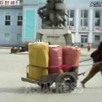 A female porter pulls a handcart loaded with overflowing sacks. (In front of Hyesan Railway Station. Hyesan, Ryanggang Province. October, 2013) ASIAPRESS