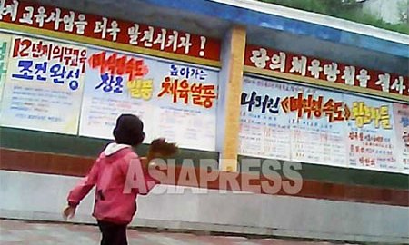 A public board filled with slogans praising the implementation, by the Kim Jong-un administration, of a new system of twelve-year compulsory education. (August 2013. Photo capture from the video footage filmed in a northern city of North Korea)  ASIAPRESS