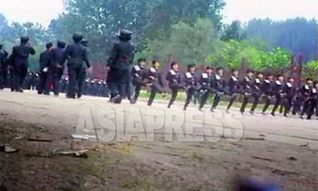 This picture is taken from raw video footage captured in Sosong District, Pyongyang in the summer of 2006. Female students are assembled near the Three Revolution Exhibition museum to practice for a military parade in honor of Kim Jong-il's birthday. Each student is wearing a white shoulder-cloth inscribed with a consecutive number. (Lee Jun / Pyongyang / August 2006) ASIAPRESS