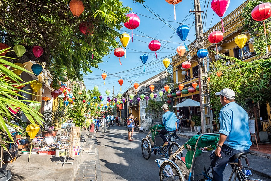 Tourists travel by cyclo to admire the beauty of the lantern street