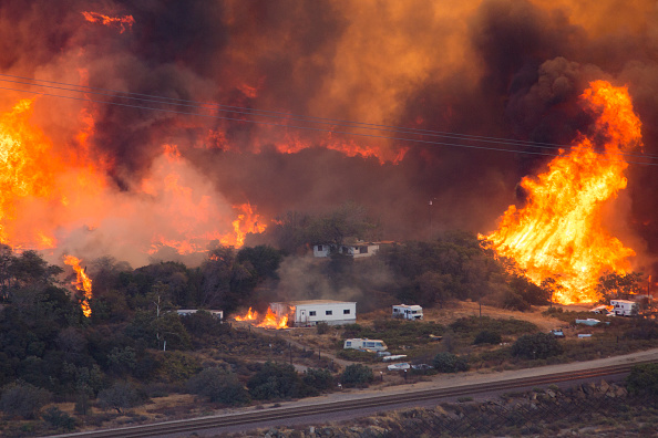 WRIGHTWOOD, CA - AUGUST 17: Flames sweep through a rural community at the Blue Cut Fire on August 17, 2016 near Wrightwood, California.. An unknown number of homes and businesses have burned and more than 80,000 people are under evacuation orders as the out-of-control wildfire spread beyond 30,000 acres and threatens to expand into the ski resort town of Wrightwood. (Photo by David McNew/Getty Images)