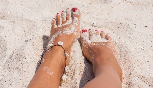Relaxing at a beach, with your feet on the white sand.