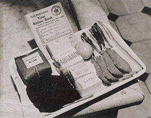 A ration book and a person's rations for a week - including four rashers of bacon and one egg.