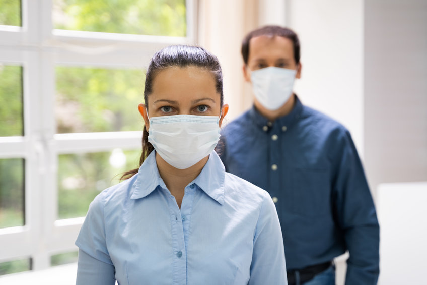 a man and woman facing camera wearing face masks