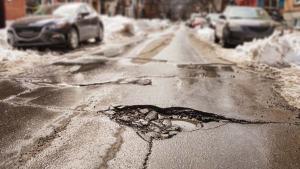 Schlagloch einer Straße im Winter welches optimal für Kaltasphalt geeignet ist