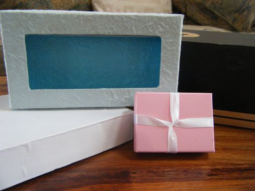 Three different sized boxes - small pink gift box, white medium box and blue slightly larger box
