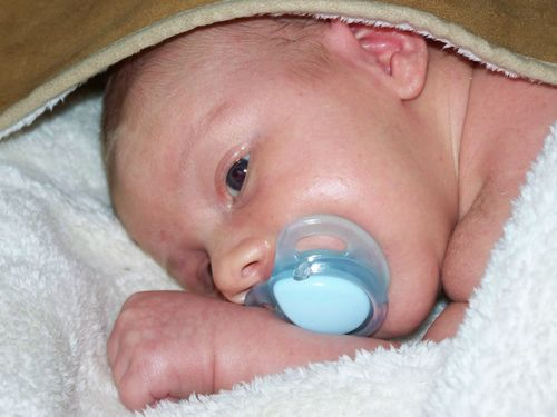 newborn baby with a dummy