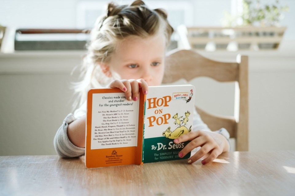 Image of a young girl sitting at a kitchen table reading the book Hop on Pop by Dr Seuss