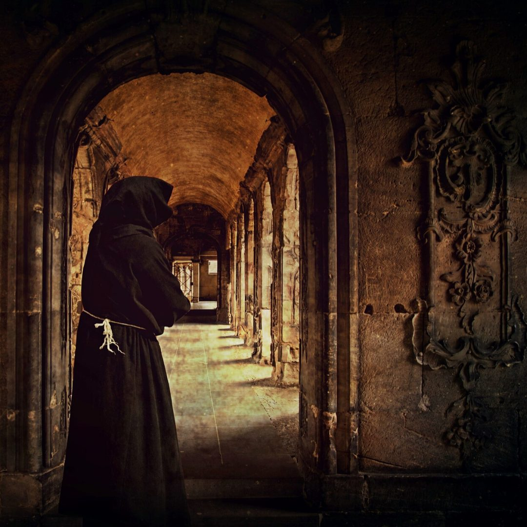 Image of a monk walking through an archway in an abbey