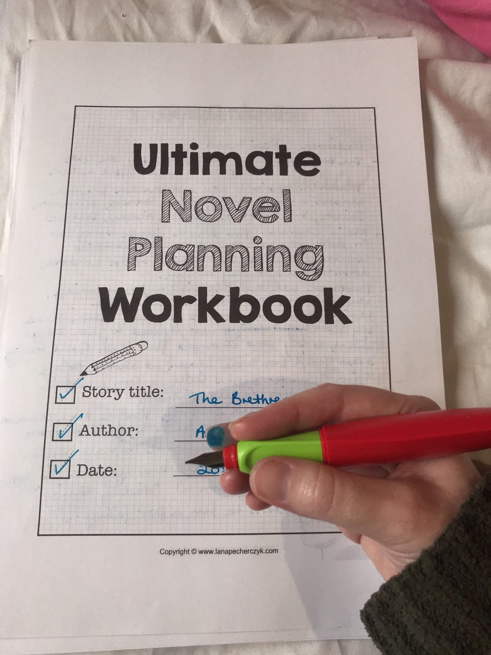 "Image of a printed A4 document entitled ""Ultimate Novel Planning Workbook"" with a hand holding a fountain pen over the top."