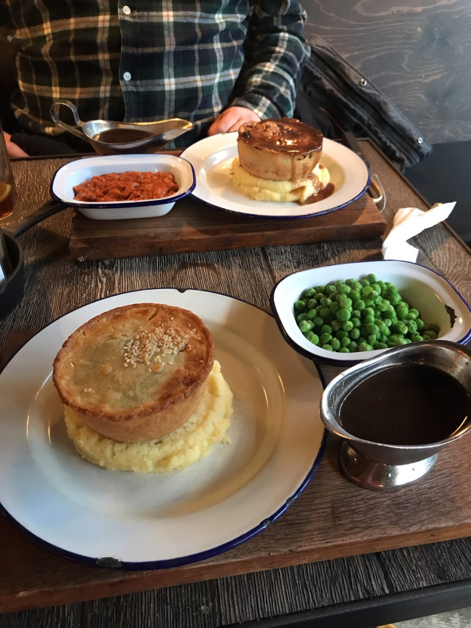 Image of two pies on a table, both sit on a bed of mashed potato on a plate, with accompaniments in separate dishes to the side. The side dishes have peas, beans, and gravy in them.
