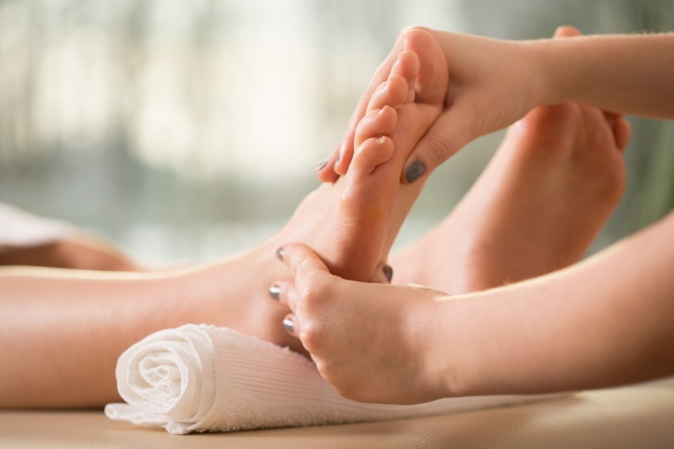 Image of a reflexology treatment, with the client's feet resting on a rolled up towel and the therapist pressing on certain areas of the sole.
