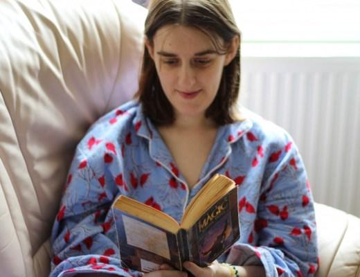 Amanda in blue pyjamas reading the book Wild Magic by Tamora Pierce