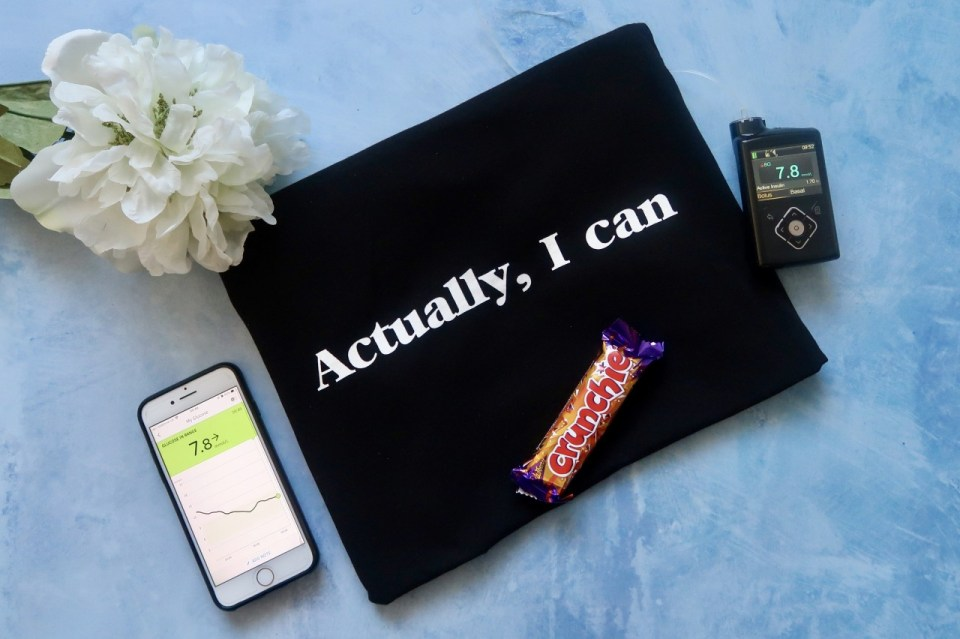 "flat lay image of items related to diabetes - blood sugar monitor and app, chocolate bar, and a bag saying, ""actually I can""."
