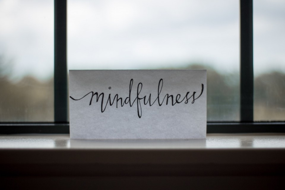 the word mindfulness written in handwritten script on a piece of paper sitting in front of a window