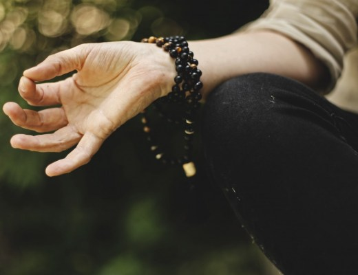 close up of a woman's hand in a mudra position with mala beads wrapped around her wrist
