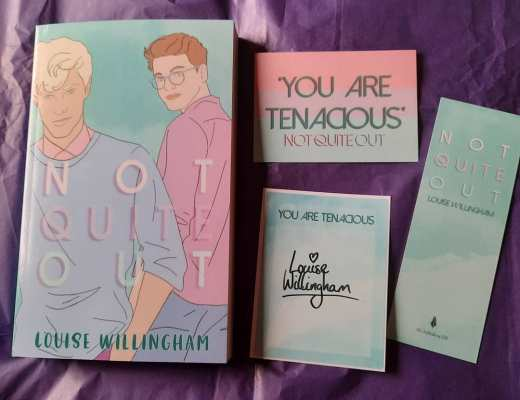 "The book Not Quite Out by Louise Willingham, which has a pale blue front cover with two white male characters drawn on it. One has blond hair and is wearing a blue sweater over a pink shirt and looking towards the reader. The second has brown hair, is wearing glasses and a pinkish purplish shirt and is walking away from the reader but looking back over his shoulder. Next to the book lay a postcard which says ""you are tenacious"" on it, with 3 horizontal bands of colour in pink, purple, and blue; a blue book plate saying the same thing and which is signed by the author and a blue bookmark with the book's title on it. They are all laying on a piece of dark purple tissue paper."