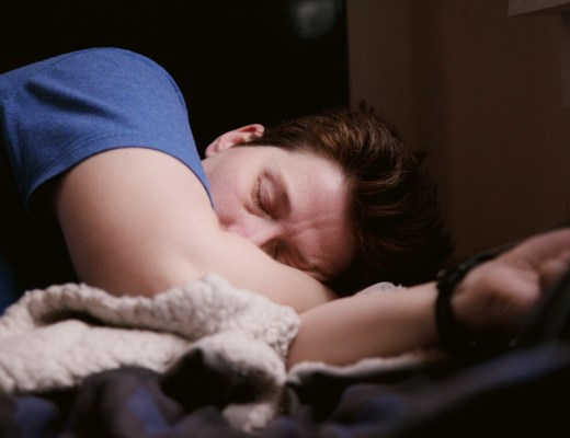 a white woman with short dark hair and wearing a blue top is laying in bed with her eye closed.