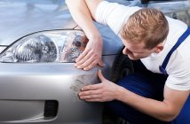 homem analisando arranhado na lataria do carro
