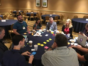 Color photo of several participants sitting around a table at Lean Coffee