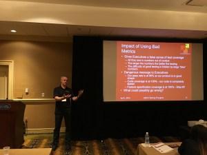 color photo of Paul Holland presenting Bad Metrics slide