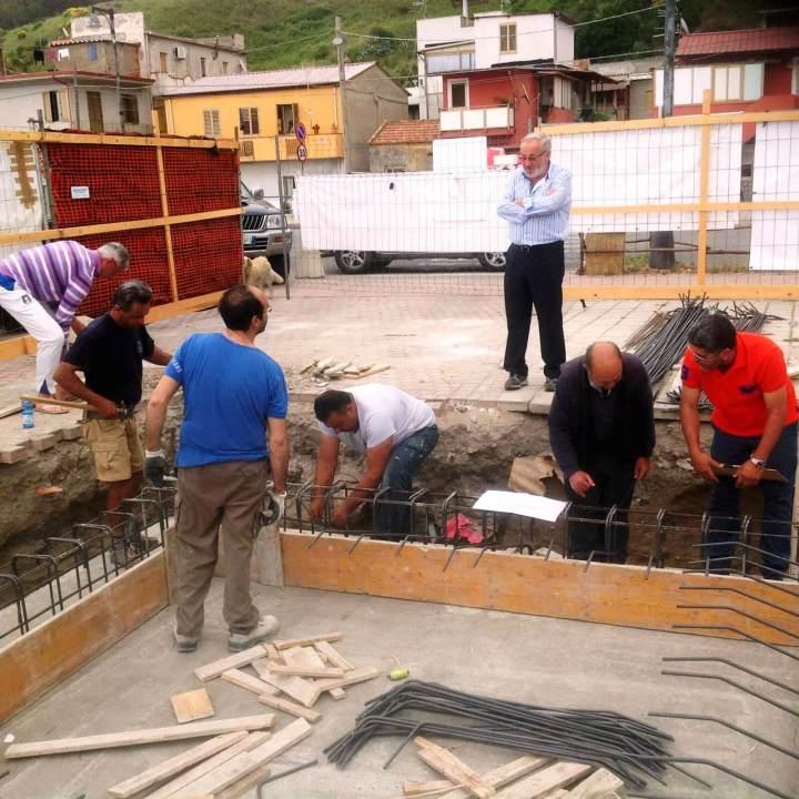 Operai che lavorano il ferro per la base del Monumento al Pescatore