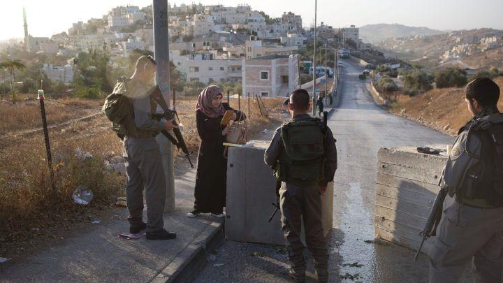 Polizia di confine israeliana controlla i documenti di una donna palestinese vicino ai blocchi di cemento appena piazzati in un quartiere di Gerusalemme Est. 15 ottobre 2015. AP.